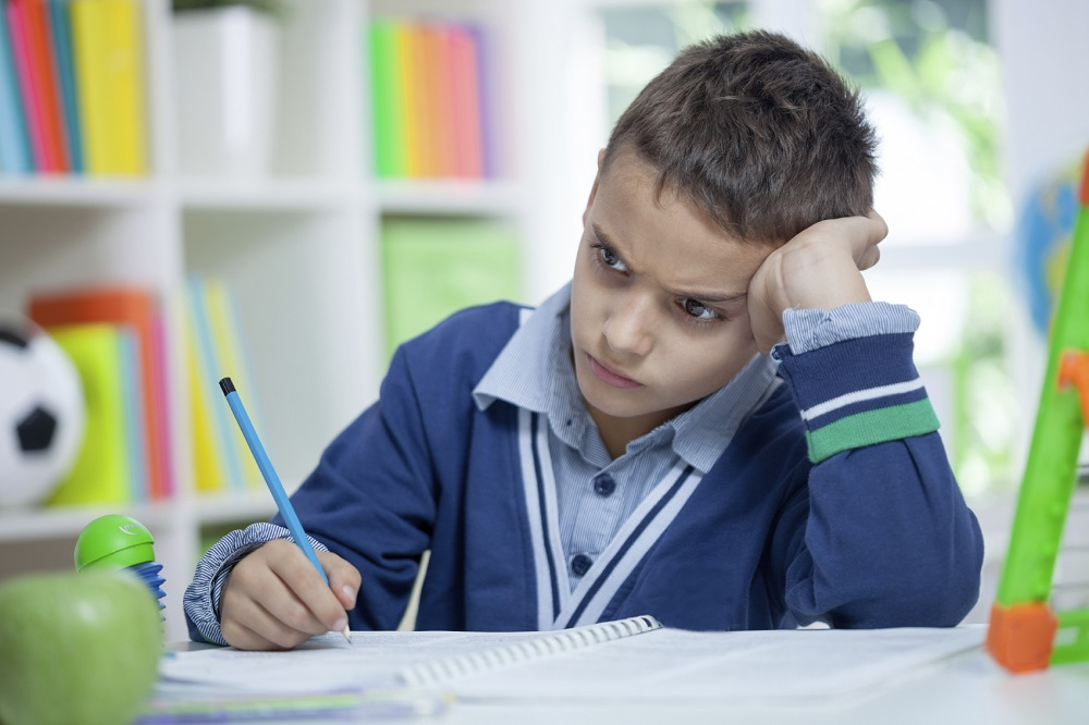 Angry and tired schoolboy studying